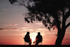 Elderly couple watching the sunset relationship